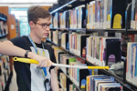 Jack Miller dusts shelves at the main location of Gail Borden Public Library District in Elgin, Illinois, pre-pandemic. (Photo: Gail Borden Public Library District in Elgin, Illinois)