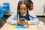 Black girl with long braids sits at school desk and looks at cellphone (Photo: RODNAE Productions/Pexels)