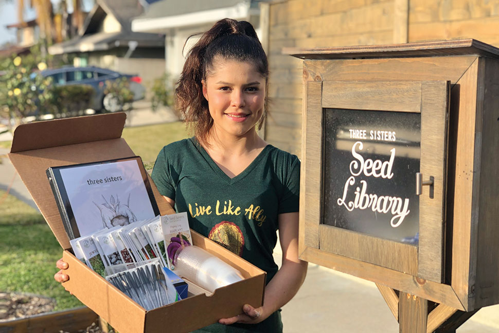 Alicia Serratos poses in front of a seed library holding a box of seeds.
