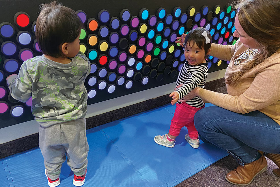 Two toddlers and an adult play with Everbright, an interactive light wall with many multicolored round dials. The smallest child faces the camera smiling.