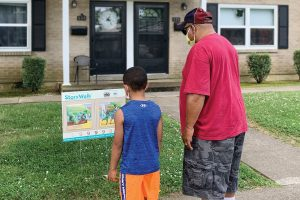 Henderson County (Ky.) Public Library's StoryWalk participants read a page from picture book Jonathan and His Mommy last summer.