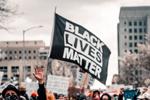 Black Lives Matter flack waves over protest (Photo: Colin Lloyd/Unsplash)
