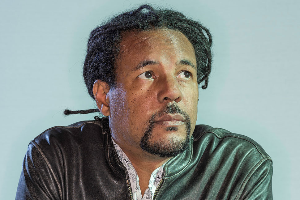 Colson Whitehead (Black man with braided hair pulled back, wearing leather jacket, looking just up and to the right)