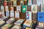 Wooden shelves of spiral-bound cookbooks by Morris Press (Sam O'Brien/Gastro Obscura)