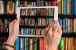Tablet held in front of library shelves (Image: Gerd Altmann/Pixabay)